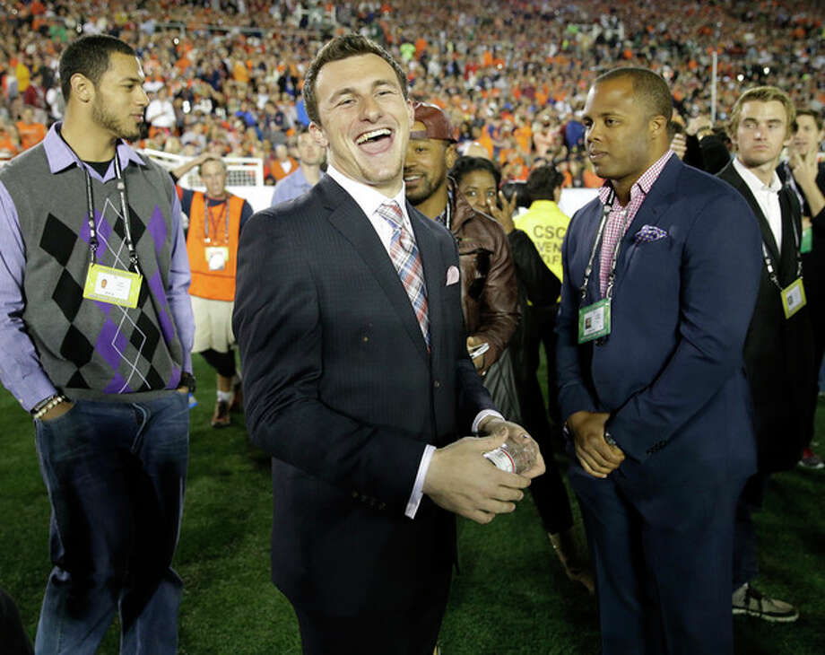 Texas A&M quarterback Johnny Manziel smiles from the sidelines during the first half of the NCAA BCS National Championship college football game between Auburn and Florida State Monday, Jan. 6, 2014, in Pasadena, Calif. (AP Photo/David J. Phillip) / AP