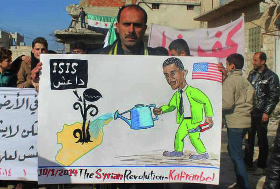 """In this citizen journalism image provided by Edlib News Network, ENN, which has been authenticated based on its contents and other AP reporting, a protester holds a placard depicting U.S. President Barack Obama during a demonstration in Kafr Nabil town, Idlib province, northern Syria, Friday, Jan. 10, 2014. Rebel-on-rebel fighting between an al-Qaida-linked group and an array of more moderate and ultraconservative Islamists has killed nearly 500 people over the past week in northern Syria, an activist group said Friday, in the most serious bout of violence among opponents of Syrian President Bashar Assad since the civil war began. The Arabic on the poster is an acronym meaning, """"the Islamic State of Iraq and the Levant."""" (AP Photo/Edlib News Network ENN) / EDLIB NEWS NETWORK ENN"""
