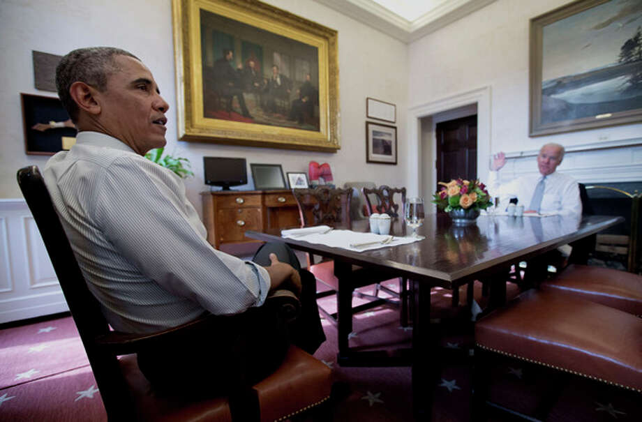 President Barack Obama and Vice President Joe Biden talk during a photo-op as they meet for lunch in the Private Dining Room of the White House in Washington, Wednesday, Jan. 8, 2014. (AP Photo/Carolyn Kaster) / AP