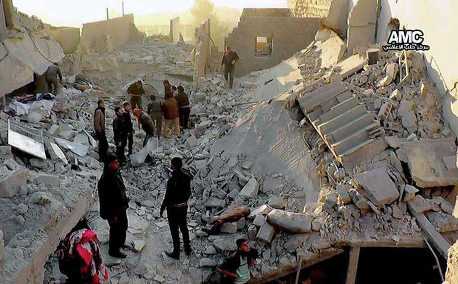 In this Monday, Jan. 6, 2014 citizen journalism image provided by Aleppo Media Center, AMC, which has been authenticated based on its contents and other AP reporting, Syrians inspect the rubble of destroyed buildings following a Syrian government airstrike in Aleppo, Syria. Syrian rebel groups battled one another Monday for control of a provincial capital, part of a vicious round of score settling targeting an al-Qaida affiliate that gained stature fighting President Bashar Assad but alienated many by imposing strict Islamic law. (AP Photo/Aleppo Media Center AMC) / Aleppo Media Center AMC