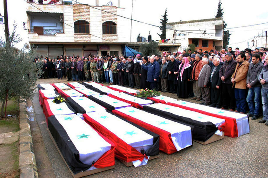 In this photo released by the Syrian official news agency SANA, Syrian citizens pray over the coffins wrapped by Syrian flags for the victims who were killed Thursday by a car bomb, during their funeral processions, at al-Kaffat village in the central Hama province, Syria, Friday, Jan. 10, 2014. Rebel-on-rebel fighting between an al-Qaida-linked group and an array of more moderate and ultraconservative Islamists has killed nearly 500 people over the past week in northern Syria, an activist group said Friday, in the most serious bout of violence among opponents of President Bashar Assad since the civil war began. (AP Photo/SANA) / SANA