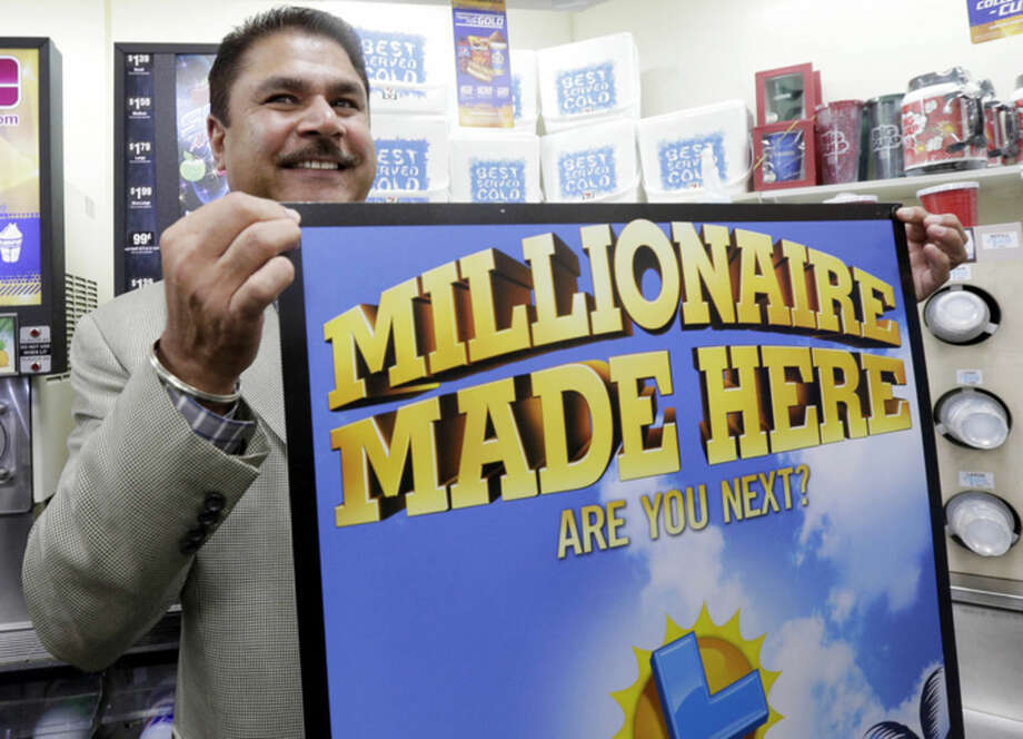 Balbir Atwal, the owner of a 7-Eleven store that sold a winning Powerball lottery ticket, holds up a Millionaire Made Here, sign at his store in Chino Hills, Calif., Thursday, Jan. 14, 2016. Atwal, says he was at home when a friend called to tell him that someone in Chino Hills had hit the jackpot. Atwal says he didn't know the ticket was purchased at his store until he turned on the TV. (AP Photo/Nick Ut)