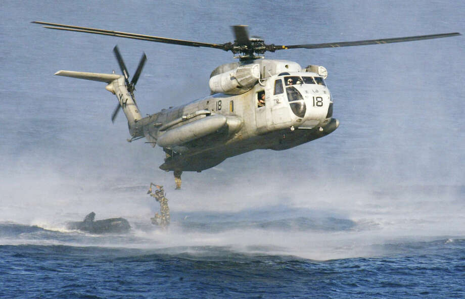 FILE - In this Feb. 18, 2003 file photo, U.S. Marines and their Philippine counterparts jump from a US Marines CH-53D Sea Stallion helicopter at Ternate in Cavite province south of Manila. The U.S. Coast Guard says two Marine helicopters have collided off the Hawaiian island of Oahu. (AP Photo/Bullit Marquez, File)