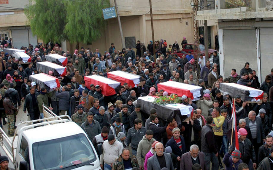 In this photo released by the Syrian official news agency SANA, Syrian citizens carry the coffins wrapped by Syrian flags for the victims who were killed Thursday by a car bomb, during their funeral processions, at al-Kaffat village in the central Hama province, Syria, Friday, Jan. 10, 2014. Rebel-on-rebel fighting between an al-Qaida-linked group and an array of more moderate and ultraconservative Islamists has killed nearly 500 people over the past week in northern Syria, an activist group said Friday, in the most serious bout of violence among opponents of President Bashar Assad since the civil war began. (AP Photo/SANA) / SANA