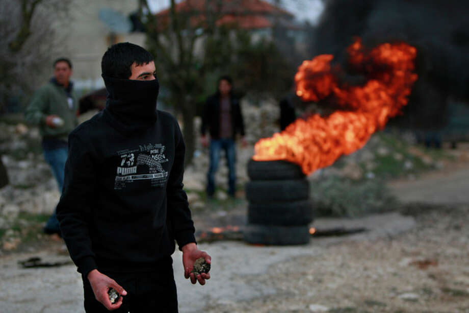 A Palestinian holds stones to hurl at Israeli forces during clashes at a protest against the expansion of the nearby Jewish settlement Ofra outside the village of Silwad, near the West Bank city of Ramallah, Friday, Jan. 10, 2014. (AP Photo/Majdi Mohammed) / AP