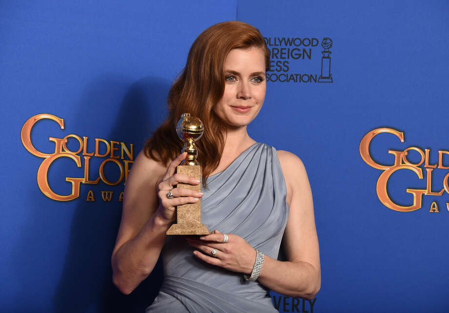 "Amy Adams poses in the press room with the award for best actress in a motion picture - musical or comedy for ""Big Eyes"" at the 72nd annual Golden Globe Awards at the Beverly Hilton Hotel on Sunday, Jan. 11, 2015, in Beverly Hills, Calif. (Photo by Jordan Strauss/Invision/AP)"
