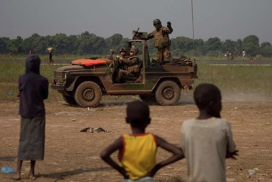 A French soldier waves to children as his jeep patrols between the airstrip and a makeshift camp housing an estimated 100,000 displaced people, at Mpoko Airport, in Bangui, Central African Republic, Thursday, Jan. 9, 2014. Embattled President Michel Djotodia who has come under growing pressure to resign, was in neighboring Chad on Thursday for a summit with regional leaders who want to end the bloodshed that has left more than 1,000 dead and nearly a million people displaced. (AP Photo/Rebecca Blackwell) / AP