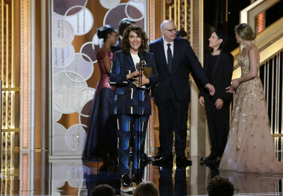"In this image released by NBC, Jill Soloway, center, accepts the award for best TV series comedy or musical for ""Transparent"" at the 72nd Annual Golden Globe Awards on Sunday, Jan. 11, 2015, at the Beverly Hilton Hotel in Beverly Hills, Calif. (AP Photo/NBC, Paul Drinkwater)"