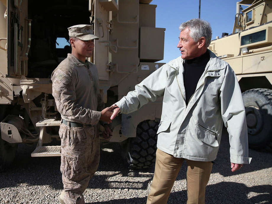 U.S. Secretary of Defense Chuck Hagel, right, shakes hands with U.S. Marine Lance CPL. Arron Corona as he works on a MRAP vehicle, at Camp Bastion, Afghanistan, Sunday, Dec. 8, 2013. Hagel spoke with troops and thanked them for being deployed for the holidays. (AP Photo/Mark Wilson, Pool) / 2013 Getty Images