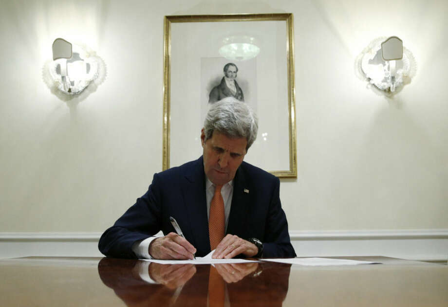 U.S. Secretary of State John Kerry signs a series of documents in Vienna, Austria, Saturday Jan. 16, 2016. U.S. Secretary of State, John Kerry confirms Iran in compliance with nuclear deal and lifts US nuclear-related sanctions. (Kevin Lamarque/Pool via AP)