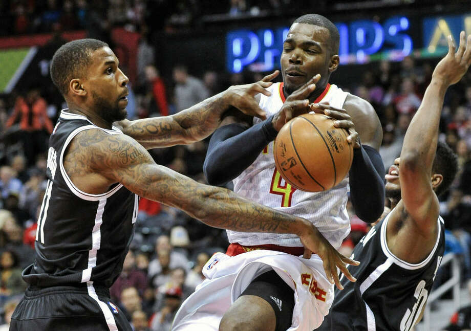 Atlanta Hawks forward Paul Millsap (4) tries to split the defense of Brooklyn Nets forward Thomas Robinson, left, and forward Thaddeus Young during the first half of an NBA basketball game, Saturday, Jan. 16, 2016, in Atlanta. (AP Photo/John Amis)