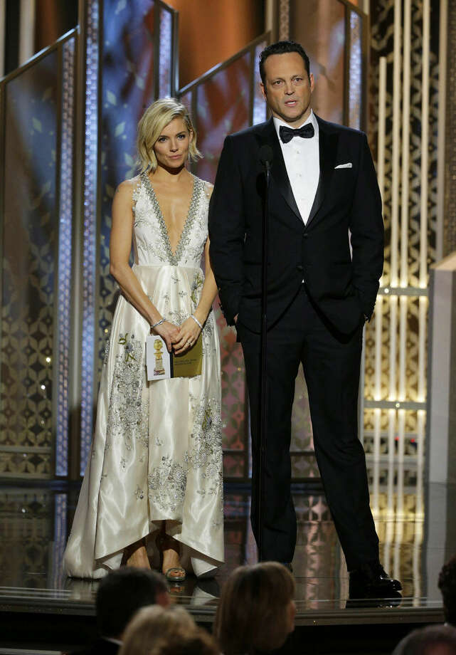 In this image released by NBC, Sienna Miller, left, and Vince Vaughn present an award at the 72nd Annual Golden Globe Awards on Sunday, Jan. 11, 2015, at the Beverly Hilton Hotel in Beverly Hills, Calif. (AP Photo/NBC, Paul Drinkwater)