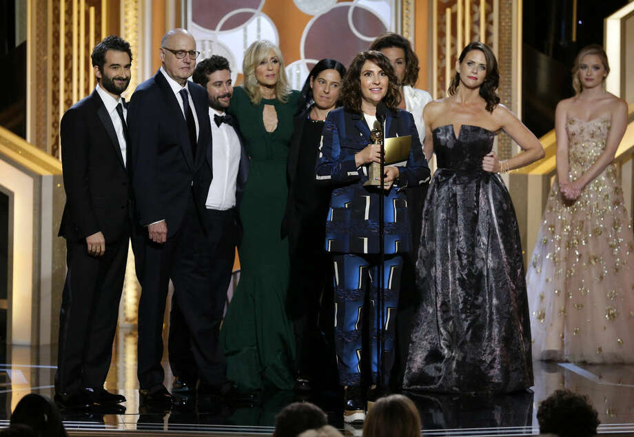 "In this image released by NBC, Jill Soloway, foreground, accepts the award for best TV series, comedy or musical for ""Transparent"" at the 72nd Annual Golden Globe Awards on Sunday, Jan. 11, 2015 at the Beverly Hilton Hotel in Beverly Hills, Calif. (AP Photo/NBC, Paul Drinkwater)"