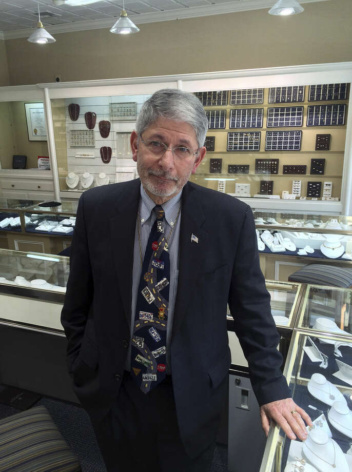 In this Thursday, Jan. 14, 2016 photo, Howard Diamond, an owner of Fairfield Center Jewelers, stands inside his store in Fairfield, Conn. Diamond is among those in town who are worried about the impact the city will suffer when General Electric moves its headquarters from Fairfield to Boston. (AP Photo/Michael Melia)