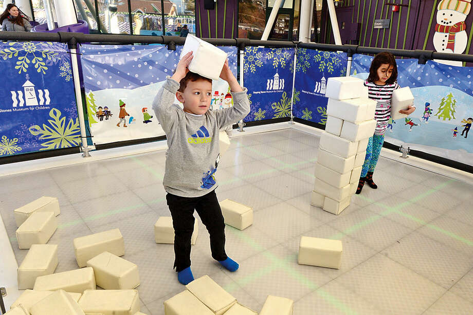 Hour photo / Erik Trautmann Jackson Reid, 5, carries blocks in the Sock Skating Rink exhibit at Stepping Stones Museum for Children Saturday. Stepping Stones will be hosting the Association of Children's Museums InterActivity 2016 conference, Collective Impact, this May.