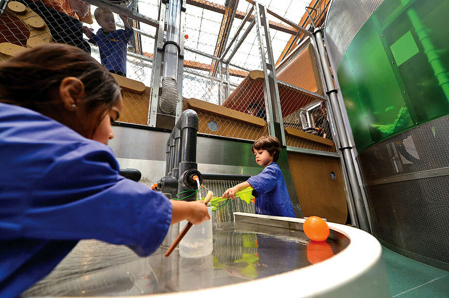 Hour photo / Erik Trautmann Ailin Cancho, 3, left, and Gianluca Baldinucci, 3, interact with the exhibits at Stepping Stones Museum for Children Saturday. Stepping Stones will be hosting the Association of Children's Museums InterActivity 2016 conference, Collective Impact, this May.