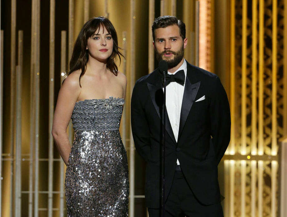In this image released by NBC, Dakota Johnson, left, and Jamie Dornan present an award at the 72nd Annual Golden Globe Awards on Sunday, Jan. 11, 2015 at the Beverly Hilton Hotel in Beverly Hills, Calif. (AP Photo/NBC, Paul Drinkwater)