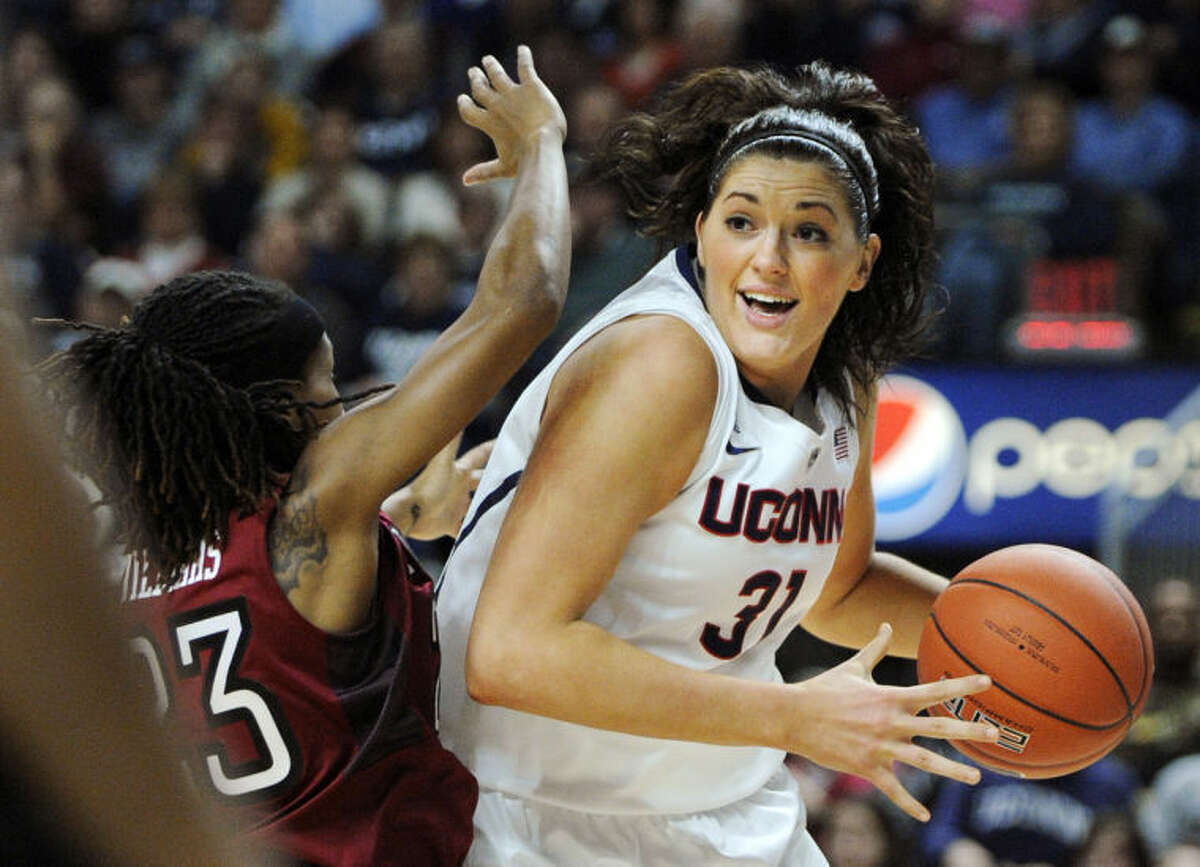 Connecticut's Stefanie Dolson (31) drives past Temple's Tyonna Williams (23) during the first half of an NCAA college basketball game in Bridgeport, Conn., Saturday, Jan. 11, 2014. (AP Photo/Fred Beckham)