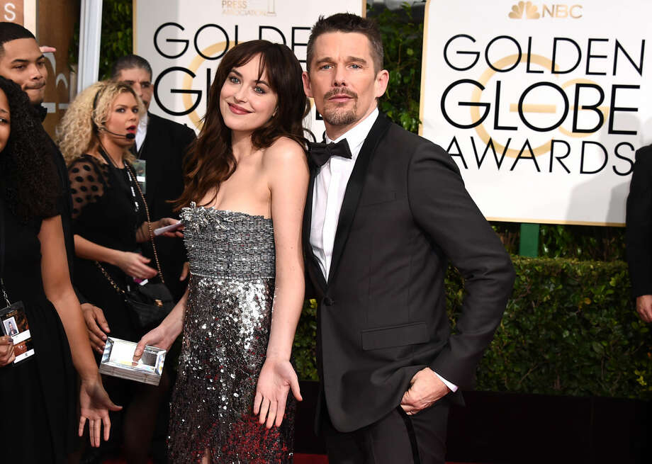 Dakota Johnson, left, and Ethan Hawke arrive at the 72nd annual Golden Globe Awards at the Beverly Hilton Hotel on Sunday, Jan. 11, 2015, in Beverly Hills, Calif. (Photo by Jordan Strauss/Invision/AP)