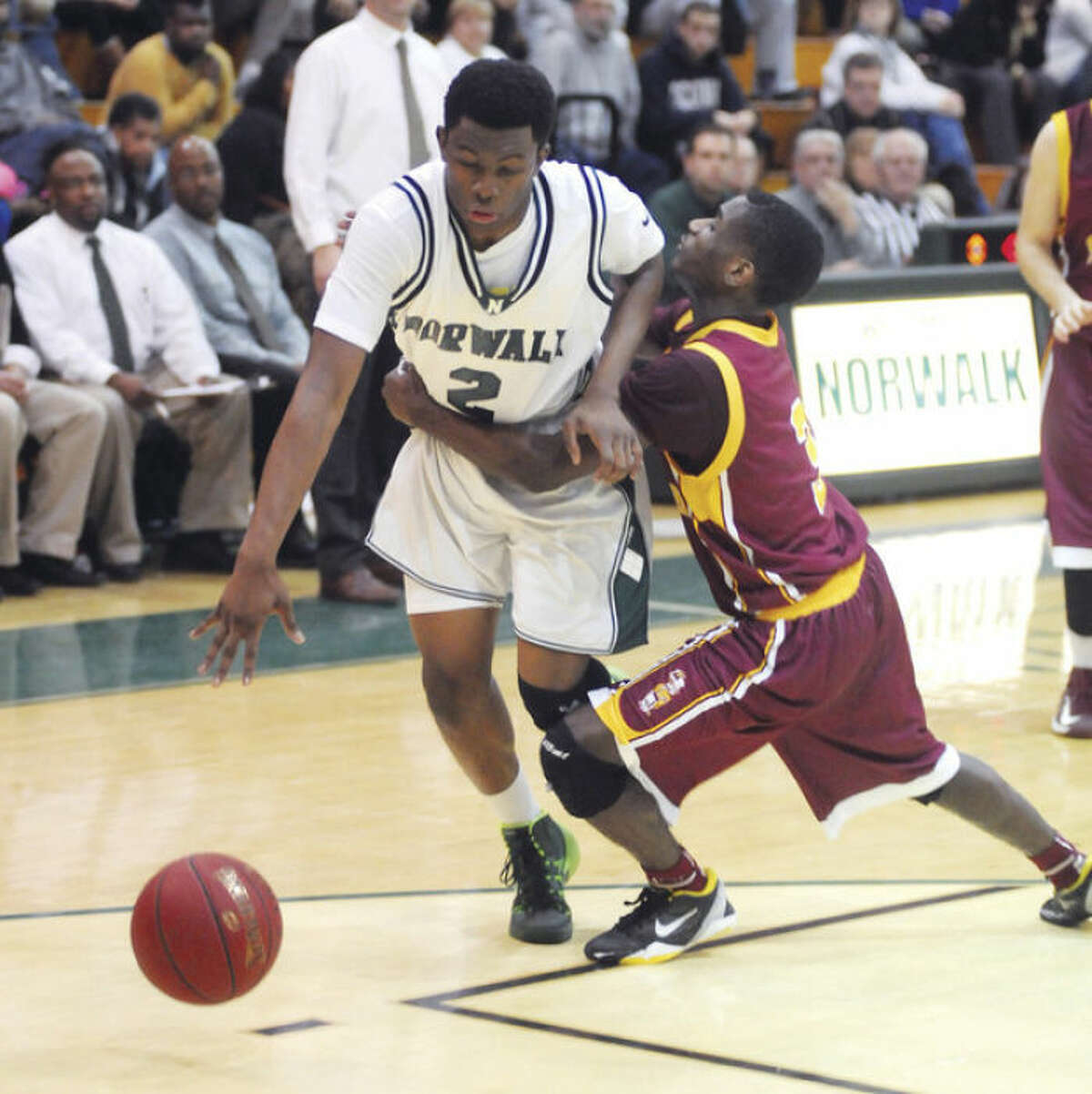 Hour photo/John Nash Norwalk's Zaire Wilson, left, is fouled by St. Joseph guard Raekwon Reid during the fourth quarter of Friday's game at Scarso Gym.