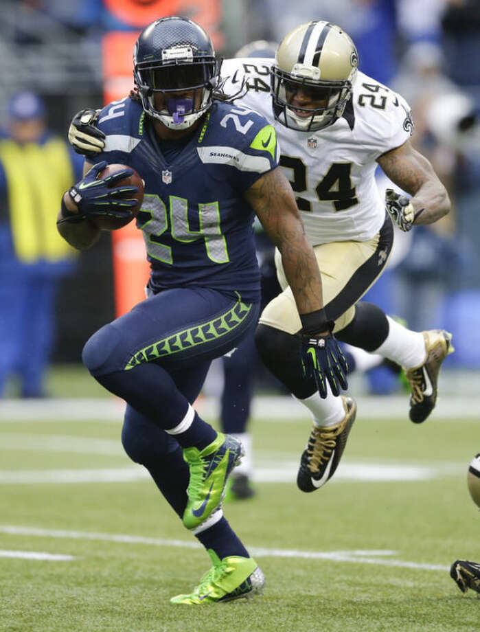 Seattle Seahawks running back Marshawn Lynch (24) runs for a 15-yard touchdown in front of New Orleans Saints cornerback Corey White during the second quarter of an NFC divisional playoff NFL football game in Seattle, Saturday, Jan. 11, 2014. (AP Photo/Ted S. Warren)