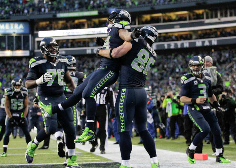 Seattle Seahawks running back Marshawn Lynch (24) celebrates with tight end Zach Miller (86) after running for a 31-yard touchdown against the New Orleans Saints during the fourth quarter of an NFC divisional playoff NFL football game in Seattle, Saturday, Jan. 11, 2014. (AP Photo/John Froschauer) / FR74207 AP