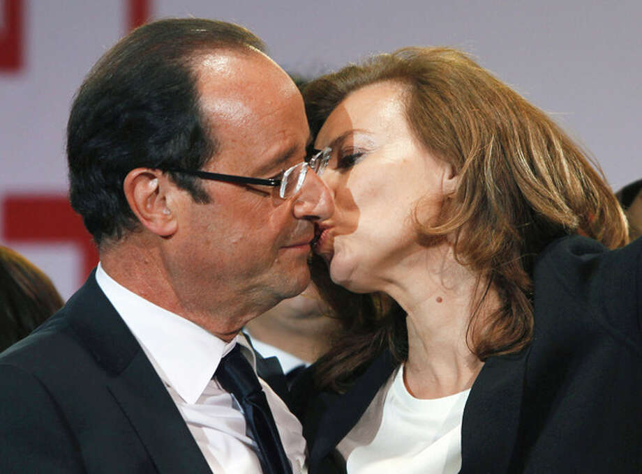 FILE - This Sunday, May 6, 2012, file photo shows French president-elect Francois Hollande kissing his companion, Valerie Trierweiler, after greeting crowds gathered to celebrate his election victory in Bastille Square in Paris. Hollande is threatening legal action over magazine report saying he is having a secret affair with a French actress. The magazine Closer published images Friday Jan.10, 2014 showing his bodyguard and a helmeted man it says is Hollande visiting what it says is the apartment of the actress. (AP Photo/Francois Mori, File) / AP