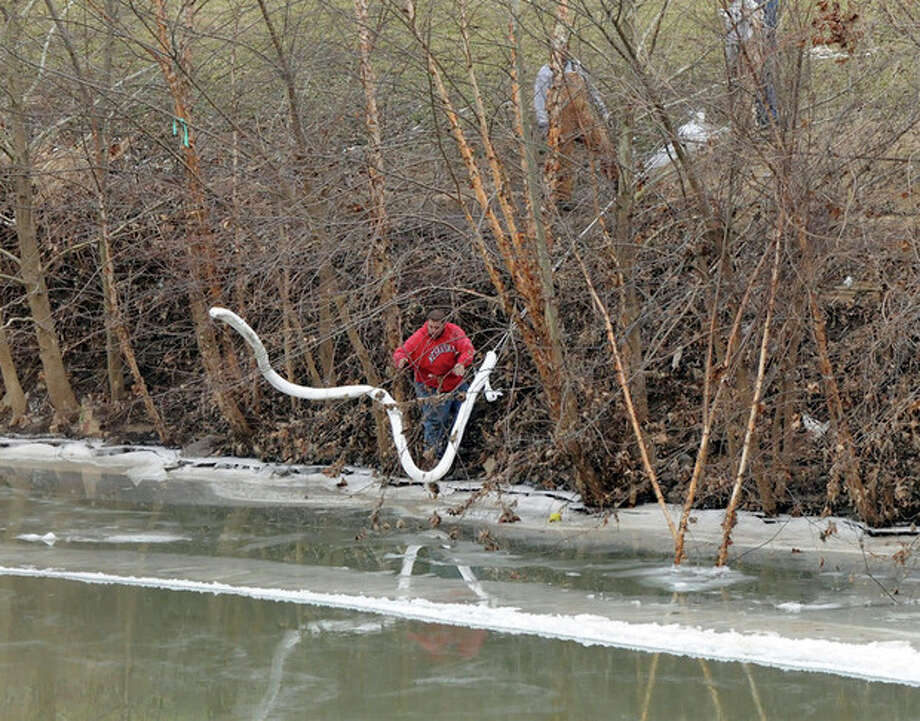 A Freedom Industries worker places a boom in the Elk River Thursday, Jan. 9, 2014, at the site of a chemical leak in Charleston that has fouled the drinking water in five West Virginia counties. (AP Photo/The Charleston Gazette, Chris Dorst) / The Charleston Gazette