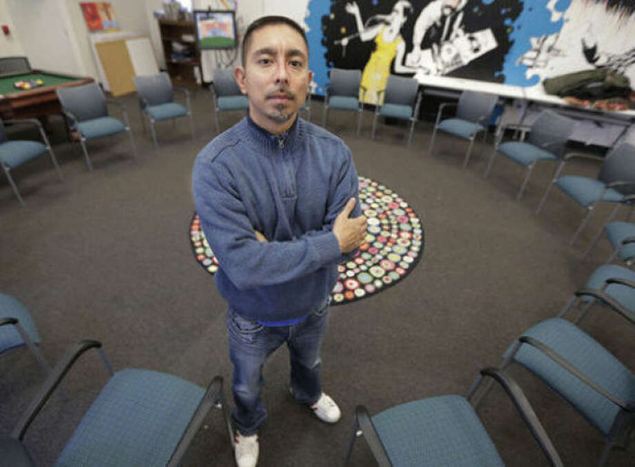 "In this Dec. 6, 2013 photo, Eddie Bocanegra, co-executive director of the YMCA of Metropolitan Chicago's Youth Safety and Violence Prevention program, stands in a ""peace circle"" at the organization's center in the Pilson neighborhood of Chicago. His understanding of kids and violence stems from his own history. He spent 14 years in prison for a gang-related murder, turned his life around and is now a graduate student at the University of Chicago. Through the Y, he mentors kids in communities where gangs are a constant presence. (AP Photo/M. Spencer Green)"