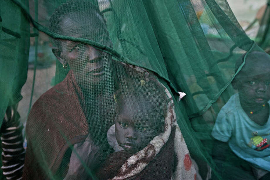 FILE - In this Thursday, Jan. 2, 2014 file photo, one of the few to have a mosquito net, a displaced family who fled the recent fighting between government and rebel forces in Bor by boat across the White Nile, sit under it after waking up in the morning in the town of Awerial, South Sudan. Sub-Saharan Africa has seen a very violent start to 2014 with raging conflicts in South Sudan and Central African Republic - the death tolls are huge and the individual incidents gruesome, with one estimate saying nearly 10,000 have been killed in South Sudan in a month of warfare. (AP Photo/Ben Curtis, File) / AP