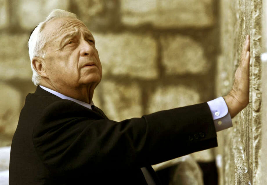 "AP file photo / David GuttenfelderIn this Feb. 7, 2001 file photo, Ariel Sharon, then Israel's Prime Minister-elect, looks up as he touches Judaism holiest site, the Western Wall, in Jerusalem. The son of former Israeli Prime Minister Ariel Sharon says his father has died on Saturday. The 85-year-old Sharon had been in a coma since a debilitating stroke eight years ago. His son Gilad Sharon said, ""He has gone. He went when he decided to go."""