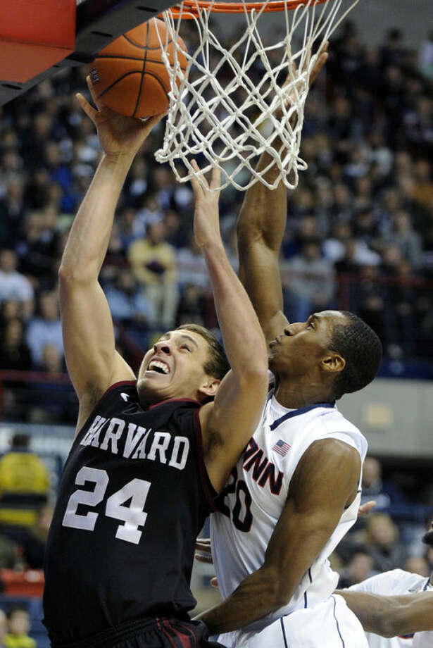 Harvard's Jonah Travis (24) drives past Connecticut's Lasan Kromah (20) during the first half of an NCAA college basketball game in Storrs, Conn., Wednesday, Jan. 8, 2014. (AP Photo/Fred Beckham)
