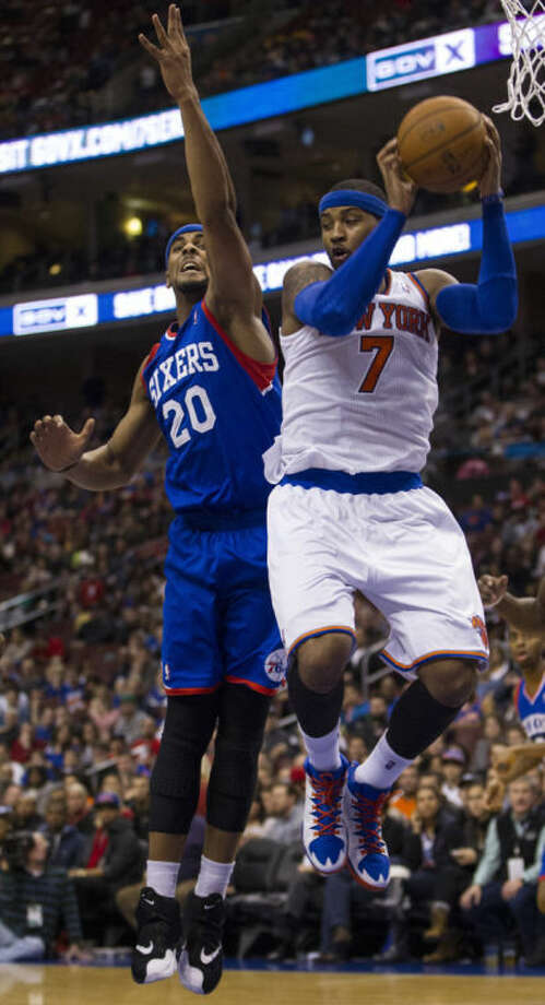 New York Knicks' Carmelo Anthony, right, pulls down the rebound over Philadelphia 76ers' Brandon Davies, left, during the first half of an NBA basketball game, Saturday, Jan. 11, 2014, in Philadelphia. (AP Photo/Chris Szagola)