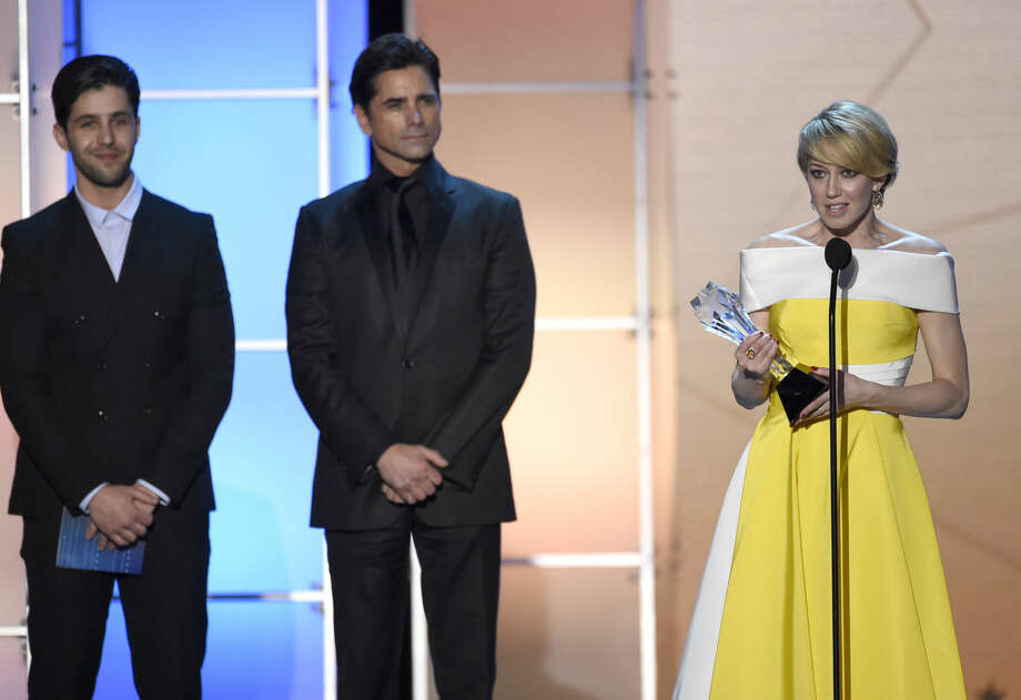 "Josh Peck and John Stamos, look on from left, as Carrie Coon accepts the award for best actress in a drama series for ""The Leftovers"" at the 21st annual Critics' Choice Awards at the Barker Hangar on Sunday, Jan. 17, 2016, in Santa Monica, Calif. (Photo by Chris Pizzello/Invision/AP)"