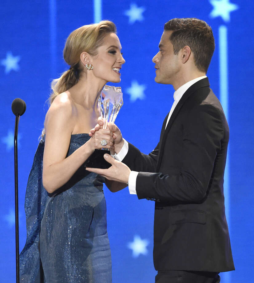 "Joanne Froggatt, left, presents the award for best actor in a drama series to Rami Malek for ""Mr. Robot"" at the 21st annual Critics' Choice Awards at the Barker Hangar on Sunday, Jan. 17, 2016, in Santa Monica, Calif. (Photo by Chris Pizzello/Invision/AP)"