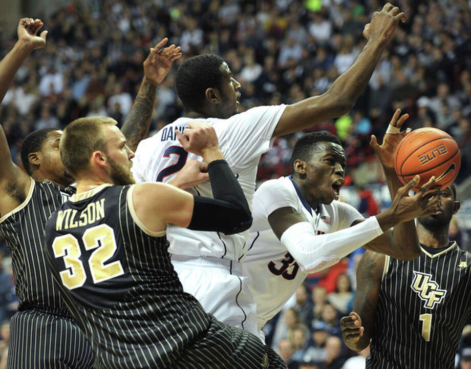 Connecticut's Amida Brimah (35), second from right, grabs a rebound beyond the reach of teammate DeAndre Daniels, third from right, Central Florida's Kasey Wilson (32) and Tristan Spurlock (1) during the first half of an NCAA college basketball game Saturday, Jan. 11, 2014, in Storrs, Conn. (AP Photo/Gretchen Ertl) / FR170046 AP