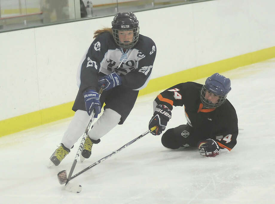 Hour photo/John NashWilton's Meghan Keating skates away from Stamford-Westhill-Staples' Kyra Dal Bello during Wednesday's game in Norwalk.