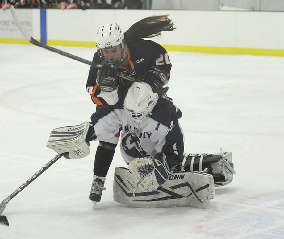 Hour photo/John NashStamford-Westhill-Staples hockey player Meg Fay, top, collides with Wilton goaltender Brooke Jonsson as the two chase down a loose puck during Wednesday's game at the SoNo Ice House in Norwalk.