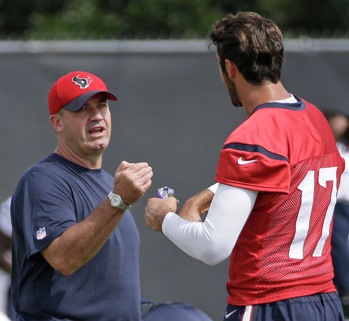 Texans head coach Bill O'Brien talks with QB Brock Osweiler during offseason workouts at NRG Park Friday, June 10, 2016, in Houston.
