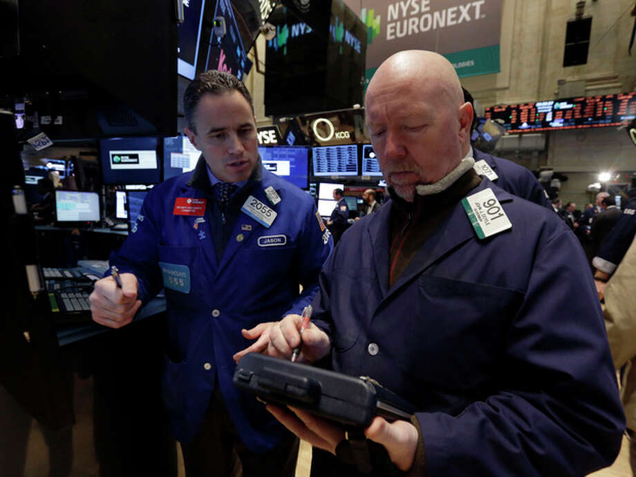 Specialist Jason Hardzewicz, left, and trader John Doyle work on the floor of the New York Stock Exchange Wednesday, Jan. 8, 2014.Stocks are mostly lower in early trading as investors hold back ahead of the release of the latest news from the Federal Reserve. (AP Photo/Richard Drew) / AP