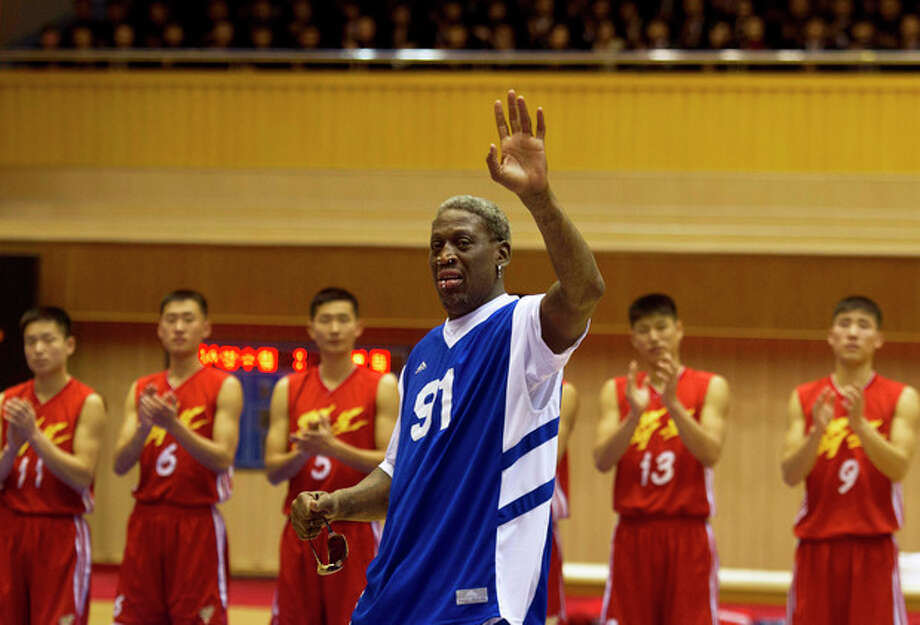 Dennis Rodman waves to North Korean leader Kim Jong Un, seated above in the stands, after singing Happy Birthday to Kim before an exhibition basketball game with U.S. and North Korean players at an indoor stadium in Pyongyang, North Korea on Wednesday, Jan. 8, 2014. (AP Photo/Kim Kwang Hyon) / AP
