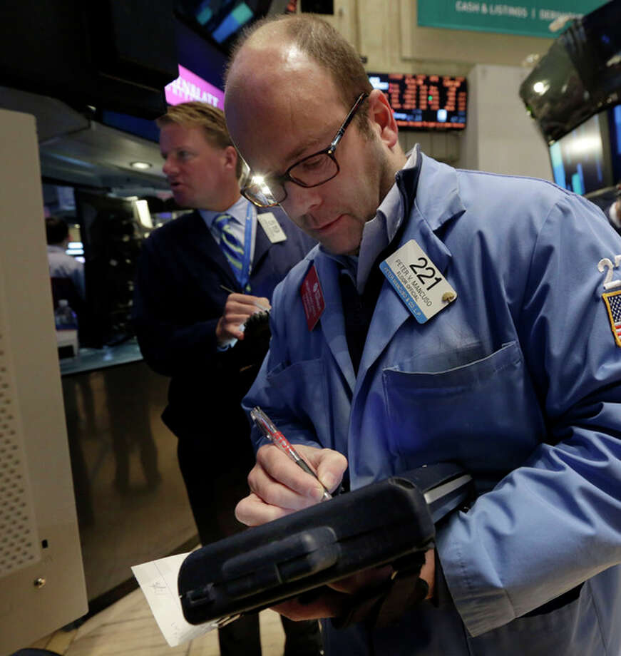 Traders John Bowers, left, and Peter Mancuso work on the floor of the New York Stock Exchange Wednesday, Jan. 8, 2014.Stocks are mostly lower in early trading as investors hold back ahead of the release of the latest news from the Federal Reserve. (AP Photo/Richard Drew) / AP
