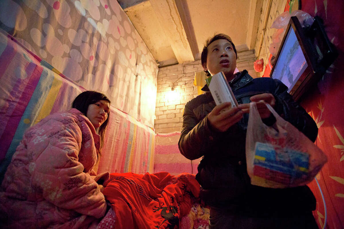 In this Jan. 4, 2014 photo, Wu Yongyuan, right, shows medicines his wife Gong Qifeng, left, takes to control her schizophrenia symptoms, in a room they rent in Beijing for stay as Wu keeps petitioning to China's central government for help. When Gong's mind is clear, she can recall how she begged for mercy. Several people pinned her head, arms, knees and ankles to a hospital bed before driving a syringe of labor-inducing drugs into her stomach. She was seven months pregnant with what would have been her second boy. The drugs caused her to have a stillborn baby after 35 hours of excruciating pain. Since the abortion more than two years ago, Gong has been diagnosed with schizophrenia. (AP Photo/Alexander F. Yuan)