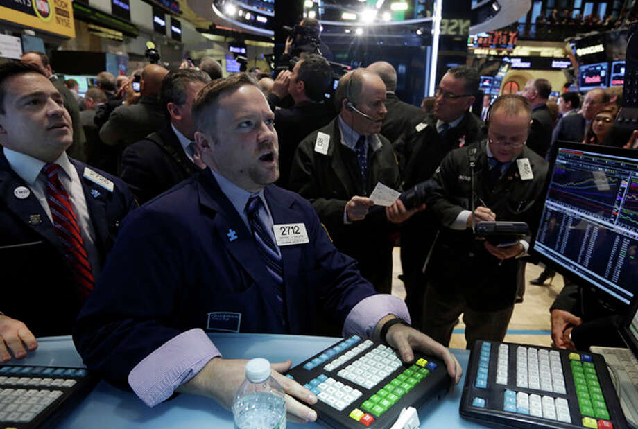 Specialist Michael Shearin, foreground center, works at his post on the floor of the New York Stock Exchange Wednesday, Jan. 8, 2014.Stocks are mostly lower in early trading as investors hold back ahead of the release of the latest news from the Federal Reserve. (AP Photo/Richard Drew) / AP
