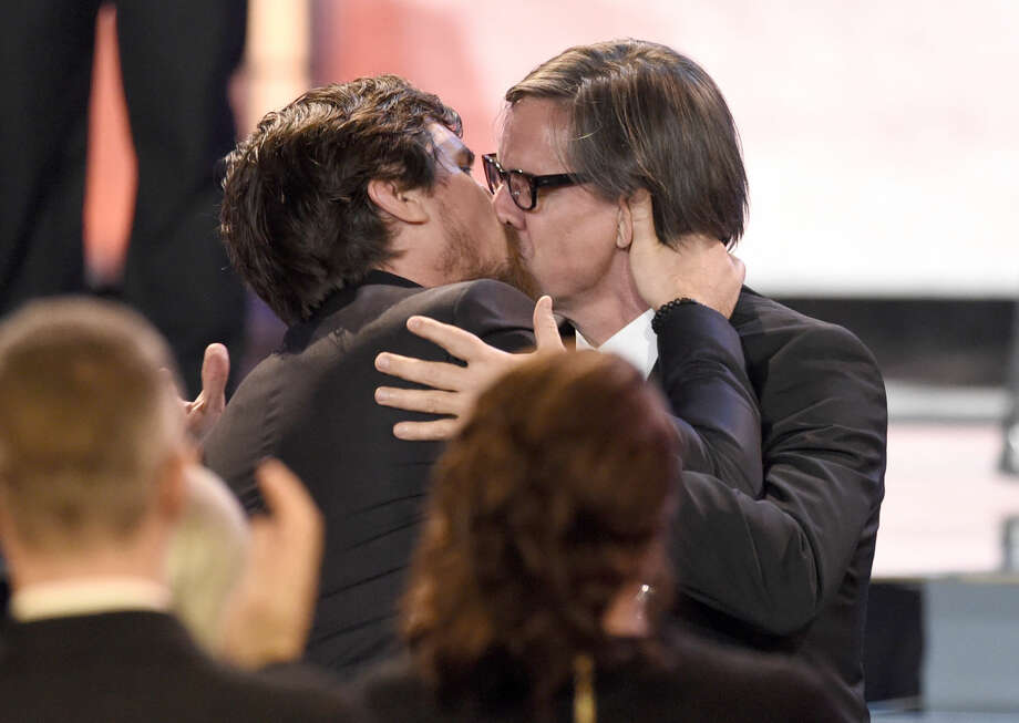"Christian Bale, left, kisses Charles Randolph as he accepts the award for best actor in a comedy for ""The Big Short"" at the 21st annual Critics' Choice Awards at the Barker Hangar on Sunday, Jan. 17, 2016, in Santa Monica, Calif. (Photo by Chris Pizzello/Invision/AP)"