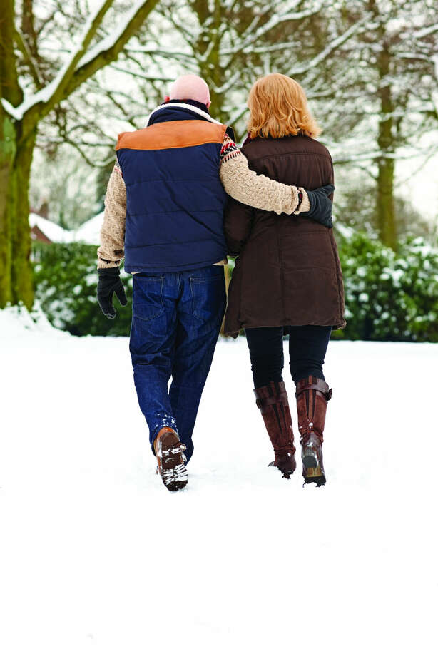 Rear view of romantinc senior couple strolling in snow