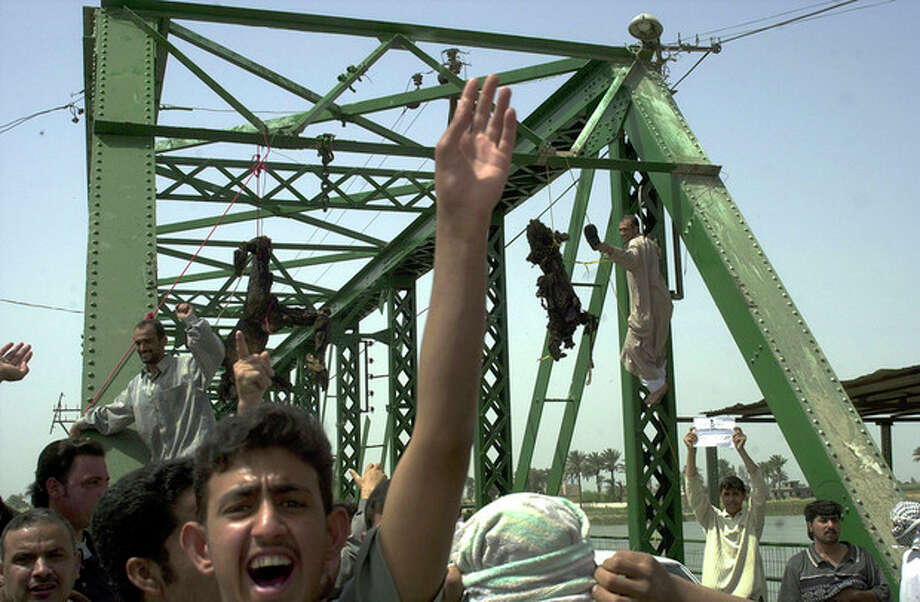 FILE - In this Wednesday, March 31, 2004 file photo, people chant anti-American slogans as charred bodies hang from a bridge over the Euphrates River in Fallujah, Iraq, west of Baghdad. Enraged Iraqis in this hotbed of anti-Americanism killed four foreigners Wednesday, and took the charred bodies from a burning SUV, dragged them through the streets, and hung them from the bridge. In 2014, the city's fall to al-Qaida-linked forces has touched a nerve for the service members who fought and bled there. (AP Photo/Khalid Mohammed) / AP