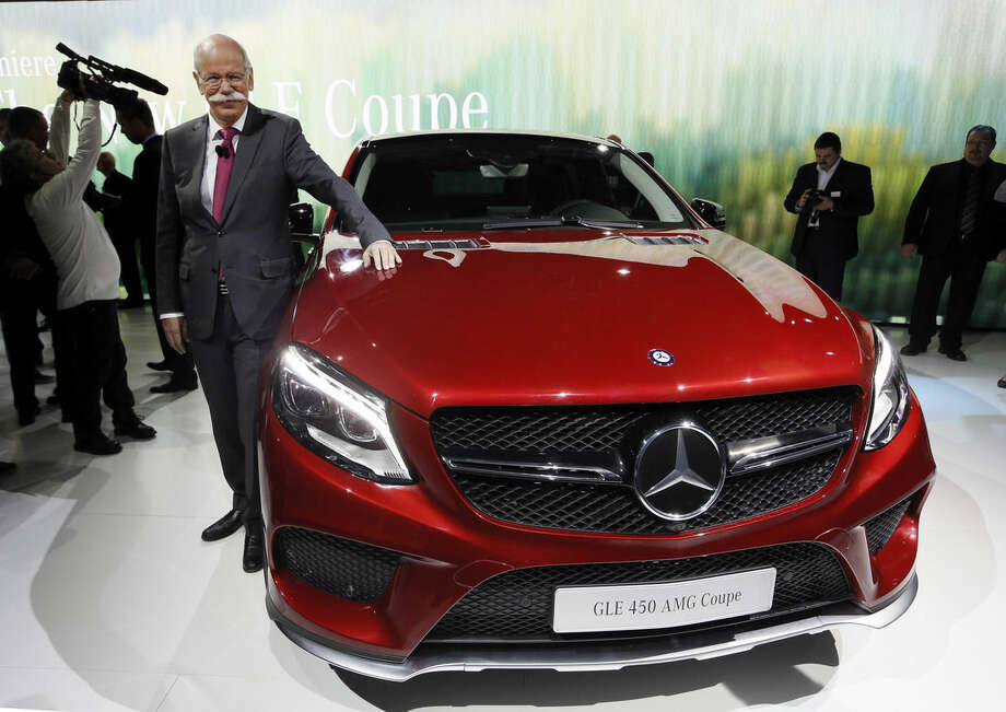 Dieter Zetsche, Chairman of the Board of Management Daimler AG, poses with the Mercedes-Benz 450 AMG GLE Coupe at media previews for the North American International Auto Show in Detroit Sunday, Jan. 11, 2015. (AP Photo/Paul Sancya)