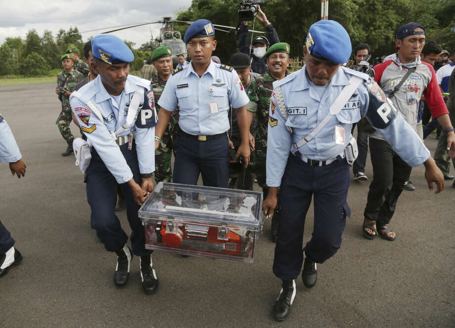 Indonesian air force personnel carry Flight data recorder of the ill-fated AirAsia Flight 8501 that crashed in the Java Sea, at airport in Pangkalan Bun, Indonesia, Monday, Jan. 12, 2015. Divers retrieved one black box Monday and located the other from the AirAsia plane that crashed more than two weeks ago, a key development that should help investigators unravel what caused the aircraft to plummet into the Java Sea. (AP Photo/Achmad Ibrahim)
