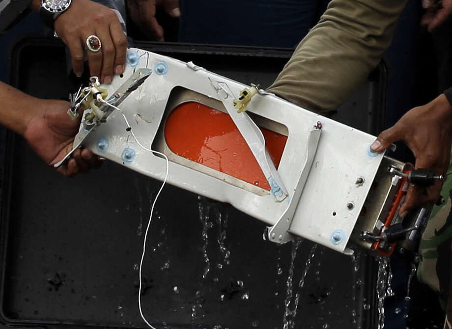 Military personnel hold a black box of the ill-fated AirAsia Flight 8501 that crashed in the Java Sea, at airport in Pangkalan Bun, Indonesia, Monday, Jan. 12, 2015. Divers retrieved one black box Monday and located the other from the AirAsia plane that crashed more than two weeks ago, a key development that should help investigators unravel what caused the aircraft to plummet into the Java Sea. (AP Photo/Achmad Ibrahim)